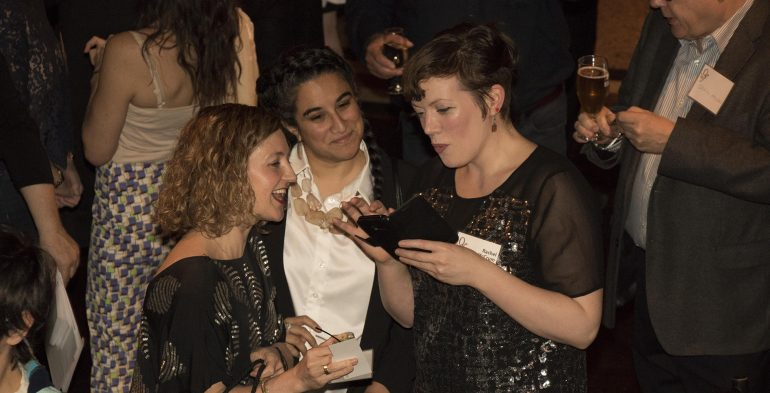 Three woman smiling while looking at an iPhone screen