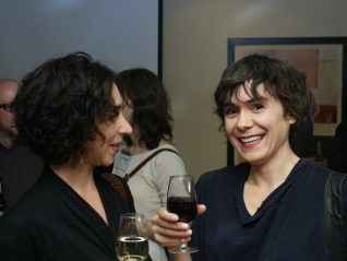 Two short haired women talking, one smiles at the camera