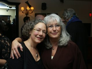 Two grey-haired, radiant women smiling at the camera