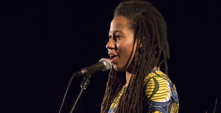 Black woman reading into a microphone