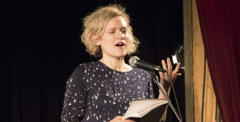 Young blond woman reading passionately at a microphone