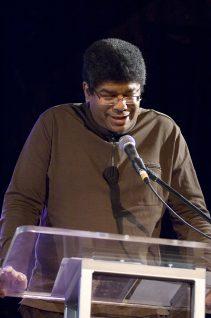 Man of colour reading at a podium