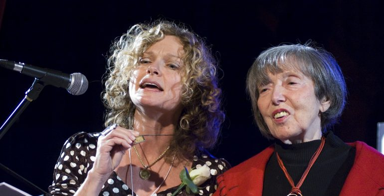 Two women singing into a microphone