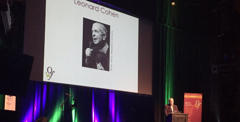 Older man speaking in front of projection of Leonard Cohen's photo
