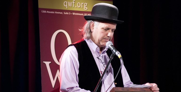 Man wearing bowler hat reading in microphone