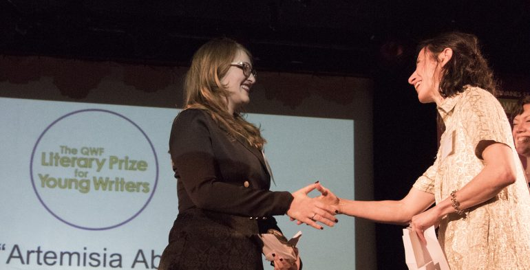 Two women shaking hands on a stage