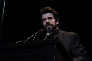 Breaded man reading at a podium