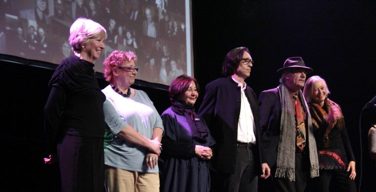 Four women and two men on stage