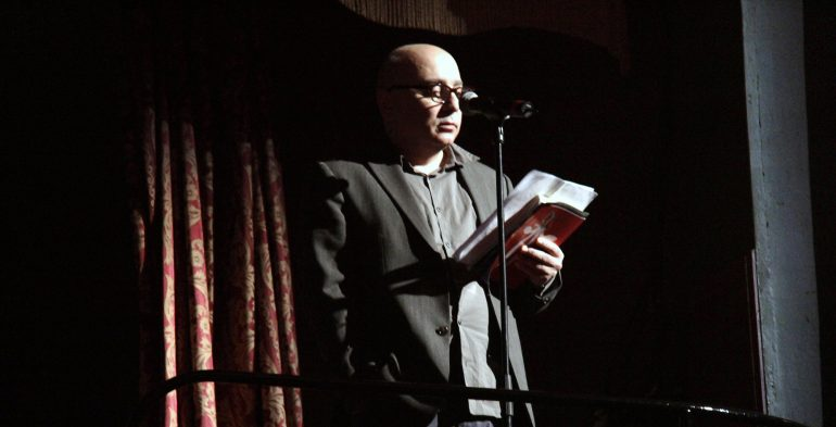Man wearing glasses reads at a microphone
