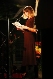 Young woman in long burgundy dress reading at a microphone