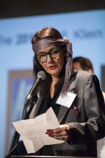 Woman wearing a purple scarf around her head reading into a microphone