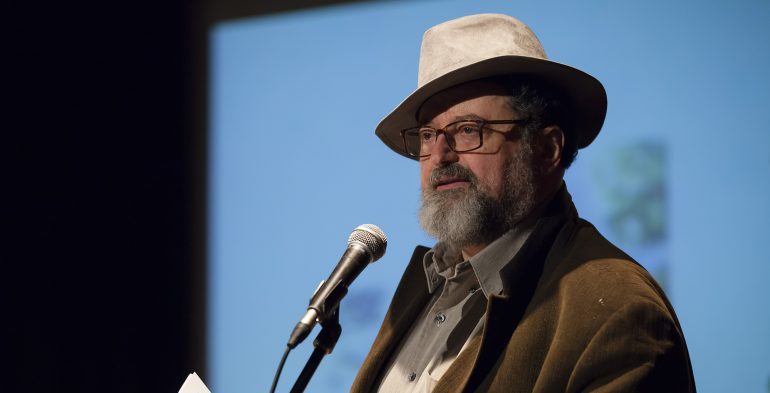 Middle aged man wearing a fedora reading at a microphone